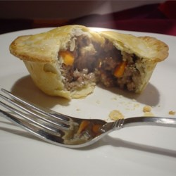 Tasty Meat Pie Recipe - This recipe makes 2 pies and is a complete meal in itself! Ground beef onion, potatoes and carrots - all sealed in with a topping of pie crust!