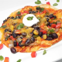 Veggie Pizzadillas Recipe - This quick and easy pizzadilla recipe features cilantro, sour cream, and queso fresco atop black beans, corn, and chile on a crisp flour tortilla.