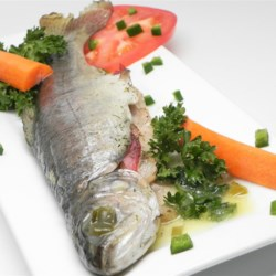 Greggae's Bacon Trout Recipe - Delicate fresh trout are seasoned with a lemon-butter sauce and stuffed with bacon and dill, then baked in foil for a tender, moist seafood dish. Bacon slices are removed before serving.