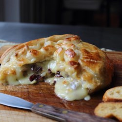 Baked Stuffed Brie with Cranberries & Walnuts Recipe - Wrapped in puff pastry dough, this baked brie with cranberries and walnuts is baked until the pastry is perfectly browned and the brie is warm and melty.