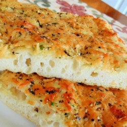 Deliciously Easy Garlic Herb Focaccia Recipe - Deliciously easy focaccia topped with garlic-infused olive oil, cheese, and herbs will be ready in 1 hour with this bread machine recipe.