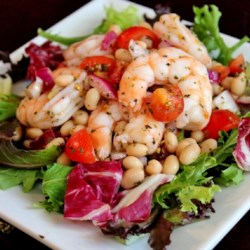 Shrimp and White Bean Salad Recipe - Shrimp, white beans, red onion, and fresh tomatoes are tossed in an Italian vinaigrette and served over salad greens for a simple and tasty option for lunch or dinner.