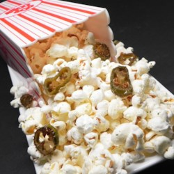 Jalapeno Popcorn Recipe - Freshly-popped popcorn is tossed with melted butter, ranch dressing mix, and crispy jalapenos for an addictive snack with a hint of heat.