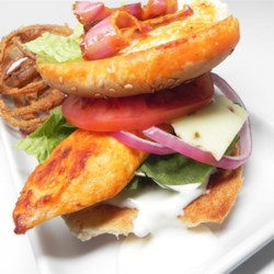 Buffalo Chicken Sandwiches Recipe - Chicken breasts broiled with regular and green hot pepper sauce, sprinkled with paprika and served on your favorite sandwich bread with lettuce and tomato.