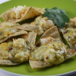 Shrimp Nachos Recipe - Shrimp is mixed in a creamy and cheesy sauce and spread on tortilla chips that are then broiled into bubbling and delicious shrimp nachos.