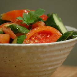 Tomato Cucumber Salad with Mint Recipe - A refreshing and simple summer salad that's perfect for picnics or barbeques. Cucumbers are marinated in red wine vinegar, sugar, salt, chopped tomatoes, red onions, mint, and olive oil; great with a spicy flank steak and potatoes.