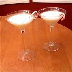 White Christmas Cocktail Recipe - A mini candy cane garnish adds a festive touch to this creamy white chocolate and peppermint cocktail.