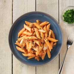 Gluten Free Penne with Chicken and Vodka Sauce Recipe - Chicken and mushrooms are simmered in a creamy vodka tomato sauce, mixed with gluten free penne and topped with Parmesan cheese.