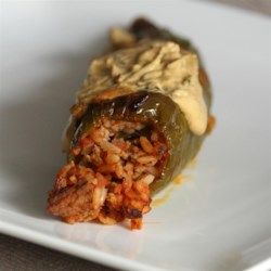 Taco Stuffed Peppers Recipe - Ground beef and Mexican rice are baked in bell peppers and topped with cheese in these taco stuffed peppers perfect for weeknight dinner.
