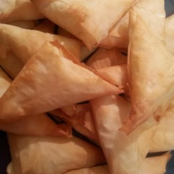 Tiropetes Recipe - Straight from Athens! Feta and Monterey Jack cheeses are mixed into a sauce with parsley and used to fill phyllo triangles in this delicious Greek appetizer.