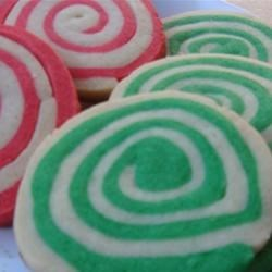 Christmas Pinwheel Cookies Recipe - Sheets of red and green butter cookie dough are rolled around each other to make a log of spiraling colors. Sliced into colorful pinwheels, these heirloom cookies are the perfect holiday treat. They can also be made in a chocolate-vanilla pinwheel variation.