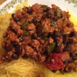 Mexican Spaghetti Squash Stir Fry Recipe - Ground turkey and black beans are simmered in Mexican-inspired seasonings and served atop roasted spaghetti squash for a quick and flavorful weeknight meal.