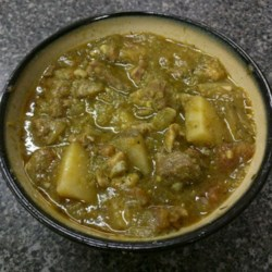 New Mexico Green Chile Stew Recipe - Green chiles, beef, and pork cubes simmer in the slow cooker with potatoes, tomatoes, herbs, and spices for a deliciously fragrant stew. It is great to serve with tortillas, tortilla chips, green onions, and sour cream.