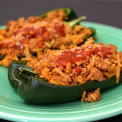 Taco Stuffed Poblano Peppers Recipe - Ground beef and Spanish rice are baked in poblano peppers that are topped with tomato gravy in this taco stuffed peppers recipe.