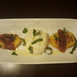 Grilled Prosciutto-Wrapped Peaches with Burrata and Basil Recipe - Peach sections wrapped in prosciutto are grilled and served with creamy burrata cheese and sliced fresh basil.