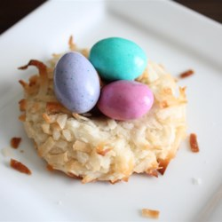 Almond Macaroon Nests Recipe - This is a tradition at Easter in our family! A delicate butter cookie, decorated with colored coconut to look like a little nest and filled with chocolate covered almonds or peanuts. I like to color the coconut by placing it into a jar with the food coloring. Just close the lid and shake until colored. No messy hands!