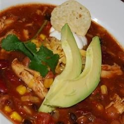 Slow Cooker Chicken Taco Soup Recipe and Video - A hearty combination of beans, corn, tomatoes, and taco seasonings, slow cooked with shredded chicken. Top each bowl with Cheddar cheese, sour cream, and crushed tortilla chips. Made mostly of canned ingredients, this tasty soup lets the slow cooker do the work so you don't have to!