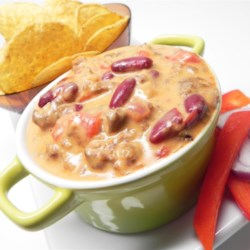Sunday Football Cheese Dip and Chips Recipe - This mixture of cheese, tomatoes, ground beef, chile peppers, and beans delivers a dip that simply belongs among your favorite football snacks.