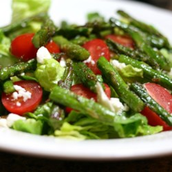 Roasted Asparagus Salad with Feta Cheese Recipe - Roasted asparagus is joined with tomatoes, feta cheese, and lettuce for a salad so flavorful you don't even need dressing.