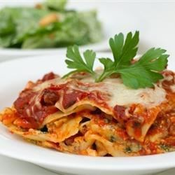 Deep Dish Lasagna Recipe - Always a crowd-pleaser: lasagna with mozzarella, ricotta, and Parmesan cheeses, sweet Italian sausage, spinach, and a homemade tomato sauce.