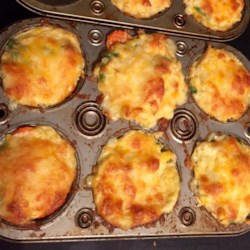 Chicken Biscuits Recipe - Prepared biscuit dough is made into small crusts containing chicken and vegetables in a creamy sauce and topped with Cheddar cheese for a fun take-along small meal or snack.