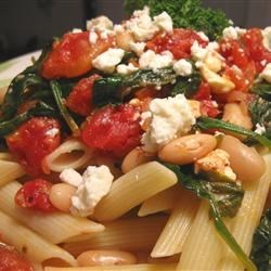 Greek Pasta with Tomatoes and White Beans Recipe - Italian-style tomatoes go for a brief simmer with tender white cannellini beans and garden-fresh spinach. Serve over hot penne and spoon crumbled bits of feta cheese over the top for a creamy sharp bite with every mouthful.