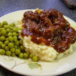 Nana's Sausage Dinner Recipe - Sausages are browned then simmered in tomato sauce before being served for dinner over mashed potatoes. My great grandmother frequently served this super quick and simple dish.