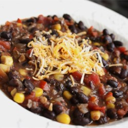 Black Bean Chili Recipe - Cooked black beans, corn, mushrooms, tomatoes, bell peppers, and onion are combined with chili powder and spices in this quick vegetarian- and vegan-friendly chili recipe.