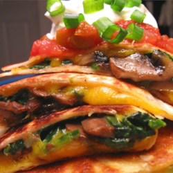 Spinach and Mushroom Quesadillas Recipe - Flour tortillas filled with creamy Cheddar cheese, portabella mushrooms, and spinach. Cut in fours and serve with guacamole and sour cream. Enjoy