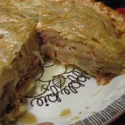Ham and Onion Pie Recipe - The filling for this double-crust pie is hearty and delicious. Lots of Jarlsberg cheese and sliced baking potatoes are layered with ham, onion and garlic. A rich egg-cream mixture is then poured over the layers and the finished pie is popped into the oven to bake up crusty brown.