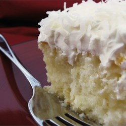 Coconut Poke Cake Recipe - White cake soaked in sweet creamy coconut milk and smothered in whipped topping and flaked coconut. A real treat for those with a sweet tooth.