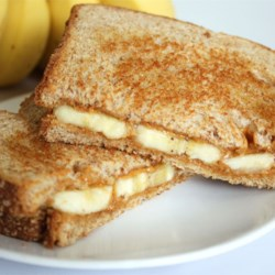 Grilled Peanut Butter and Banana Sandwich Recipe - A sweet, warm breakfast idea. Cooked like a grilled cheese, but filled with melted peanut butter and warm bananas.