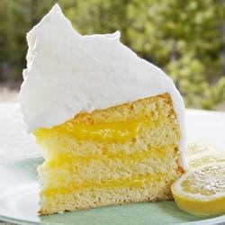 Ambrosia Cake Recipe - A light, white cake with a delicious orange-coconut filling and an almond flavored meringue frosting.