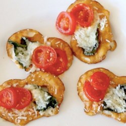 Tomato, Cheese and Basil Pretzel Crisps(R) Bites Recipe - Basil, fresh Parmesan cheese and sliced cherry tomatoes on Pretzel Crisps® make delicious appetizers.