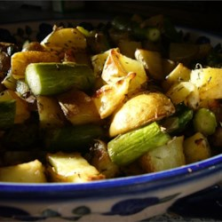 Oven Roasted Red Potatoes and Asparagus Recipe - This garlicky red potato and asparagus dish is easy and delicious served either hot or cold.  Rosemary and thyme give it a sophisticated flavor. Try adding a little chopped red pepper, too...yum!