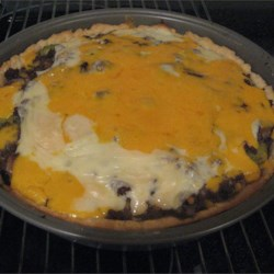 Quick Cheeseburger Pie Recipe - Pie dough takes the place of the bun in this nifty recipe. First, the dough is patted into the pie tin. The savory filling is a mix of ground beef, onion, garlic, cheese, milk, pickle juice, and a bit of flour. The pie is then baked in a hot oven and more cheese is sprinkled over the top as it bakes.
