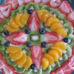 Fruit Pizza with White Chocolate Recipe - This recipe is very EASY and DELICIOUS and loved by all in my town! It is a sugar cookie crust with a milky layer of white chocolate and cream cheese, topped with your favorite fruit choices and a glaze! Substitute any fruit you like for the strawberries, and any fruit juice or juice from any canned fruits you use for the pineapple juice.