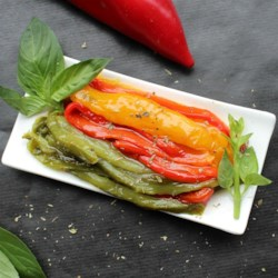 Roasted Peppers in Oil (Peperoni Arrostiti Sotto Olio) Recipe - These colorful roasted peppers are soaked in oil seasoned with garlic, basil, and oregano. Try them on sandwiches, pasta, or alone as a pretty side dish.