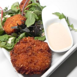Asian Crab Cake Salad Recipe - Give your crab cakes an Asian twist with this recipe using chile-garlic sauce, soy sauce, ginger, and sesame seeds to make the cakes to be served on a bed of arugula and drizzled with a spicy citrus sauce.
