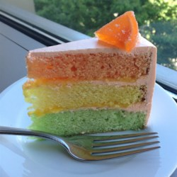 Rainbow Citrus Cake Recipe - This tri-colored cake has a lemon layer, lime layer, and an orange layer. The filling is a lemon curd and the frosting is orange.