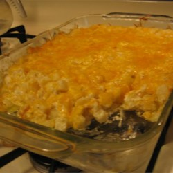 Creamy Potato Casserole Recipe - Warm and creamy cream of potato soup and sour cream are folded into hash brown potatoes, green onion and cheese. This lovely combo is then heated in the oven until the extra cheese on top melts and everything else is toasty warm.
