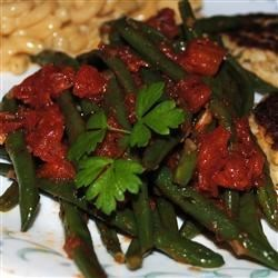 Green Beans in Tomato Sauce Recipe - Fresh green beans are tossed in garlic-infused olive oil and served in a zesty tomato sauce flavored with a hint of cumin.
