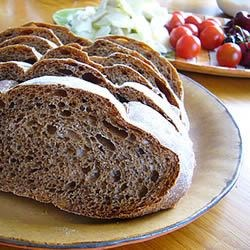 Russian Black Bread Recipe - There's a nice tangy bite to this hearty dark rye that still has a tender crumb, thanks to the wheat flour. Cocoa and coffee powders darken the loaf, and caraway and fennel seeds impart just a bit of licorice flavor. It can be made in your bread machine or with a stand mixer.