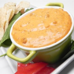 """Mexi-Cheesy Chip Dip Recipe - A definite crowd pleaser, and not too spicy for those who usually shy away from chili or salsa dips.  Served with tortilla chips.  Best served warm, but still retains a good dipping consistency when cold or at room temperature. This dip can be served in a """"bread bowl"""" (a hollowed out round loaf)."""