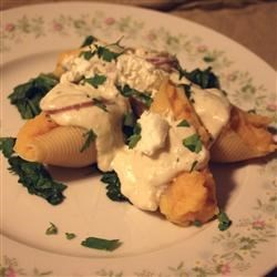 Butternut Squash Stuffed Shells Recipe - Not so Italian, but oh so delicious -- squash and goat cheese stuffed shells are perched on a bed of spinach and topped with a caramelized onion butter sauce.