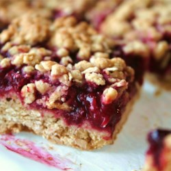 Delicious Raspberry Oatmeal Cookie Bars Recipe - Seedless raspberry jam is sandwiched between buttery brown sugar-oatmeal cookie crusts.