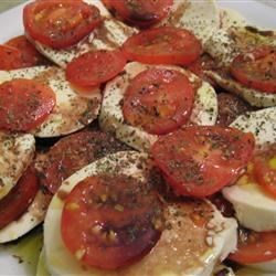Tomato Mozzarella Salad with Balsamic Reduction Recipe - This elegant green salad garnished made with fresh mozzarella, ripe slicing tomatoes, raspberries, and olives is sure to impress your guests.
