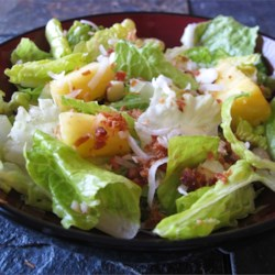 Tropical Salad with Pineapple Vinaigrette Recipe - An easy salad to make with a bag of salad greens, pineapple, bacon bits, nuts and toasted coconut.  Use fresh pineapple, if you can, and substitute toasted almonds for the macadamia nuts, if desired.