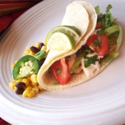 Grilled Fish Tacos with Chipotle-Lime Dressing Recipe - Marinated tilapia fillets are grilled instead of fried in this tangy, flavorful twist on fish tacos.
