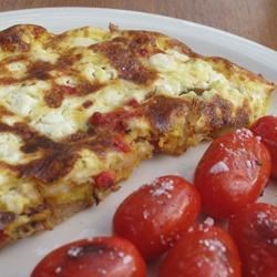 Roasted Red Pepper and Goat Cheese Frittata Recipe - Creamy eggs are poured over red potatoes and roasted red peppers in a skillet, then topped with goat cheese and finished under the broiler. A sprinkle of fresh basil gives this pretty dish extra flavor and color, so it's perfect for any special breakfast or for Christmas morning.